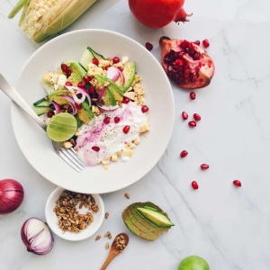 Zlim gezonde salade met avocado, mais, granaatappel, komkommer, rode ui, limoen, Griekse yoghurt en zonnebloempitten